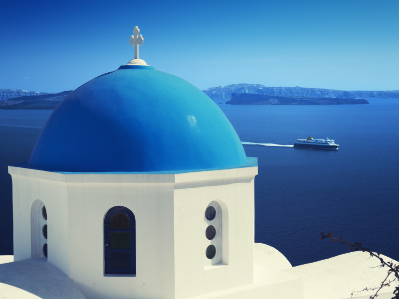 Ortodox church and ferry at Oia (Ia) village on Santorini island