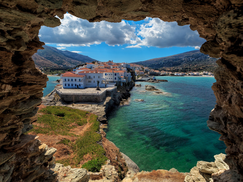 The beautiful town of Chora in Andros island, Cyclades, Greece, built on a cape, viewed from a ruin