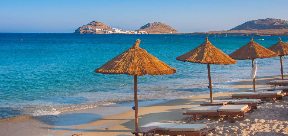 The sandy beach near the blue sea with sun beds and umbrellas. Mykonos
